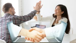 Young asian and caucasian partners giving high five at workplace, diverse motivated colleagues celebrate goal achievement