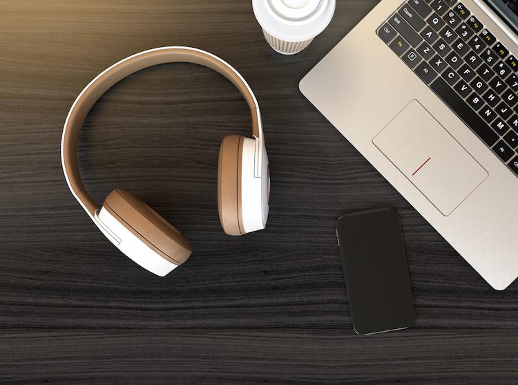 Wireless headphone, laptop PC on dark wooden table