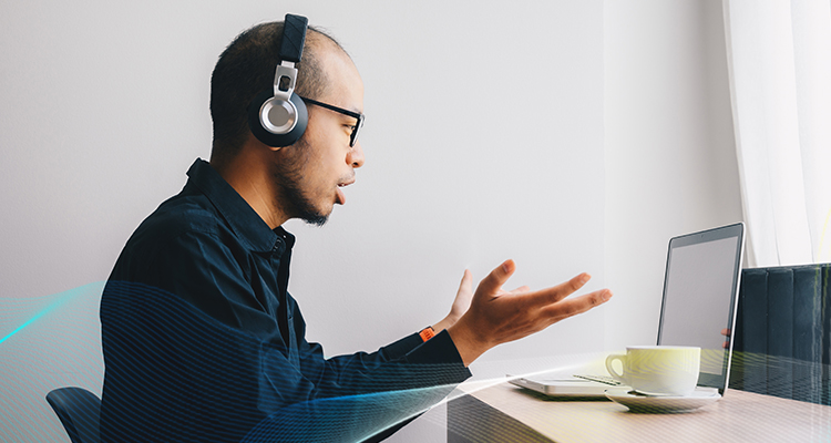 man wearing headphones and talking in front of a laptop