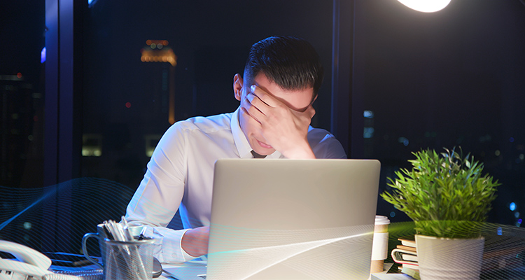 man covering his eyes with one hand and sitting in front of a computer